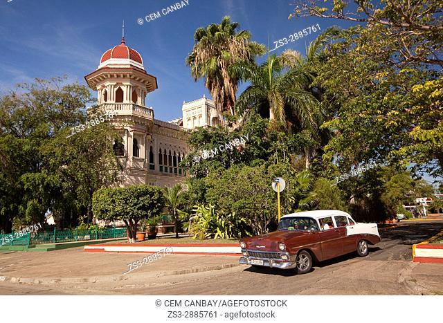 Vintage American car in front of the Palacio De Valle -Valle's Palace In Punta Gorda district, Cienfuegos, Cuba, West Indies, Central America
