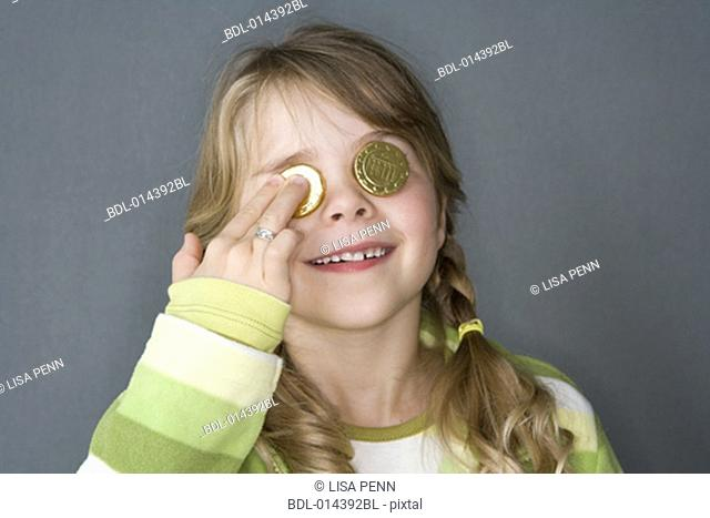 little girl in green covering her eyes with Euro coins