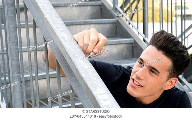 Handsome young man sitting on stairs and writing on banister or handrail, vandalizing public or private property