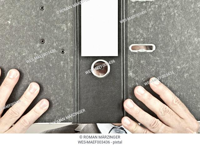 Close up of mature businessman looking through hole in ring binder