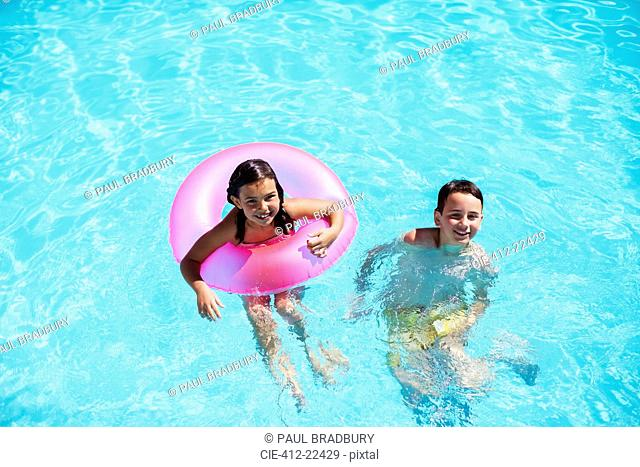 Portrait of brother and sister with pink inflatable ring in swimming pool