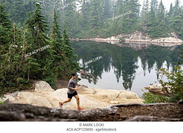 A male trail runner running through Cypress Provincial Park, British Columbia, Canada