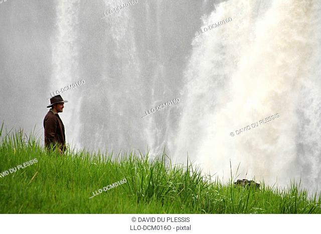 Man standing in front of main waterfall of Victoria Falls or Mosi-oa-Tunya the Smoke that thunders, Victoria Falls, Livingstone, Zambia