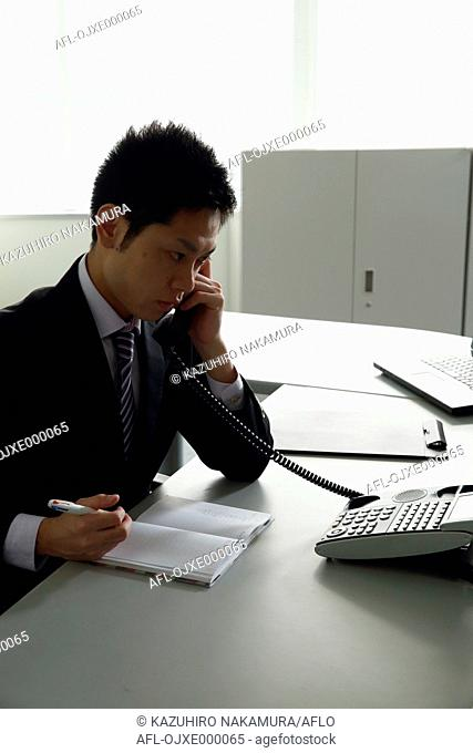 Young Japanese businessman working at his desk