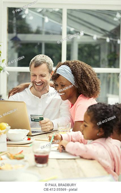 Multi-ethnic young family online shopping with credit card at laptop
