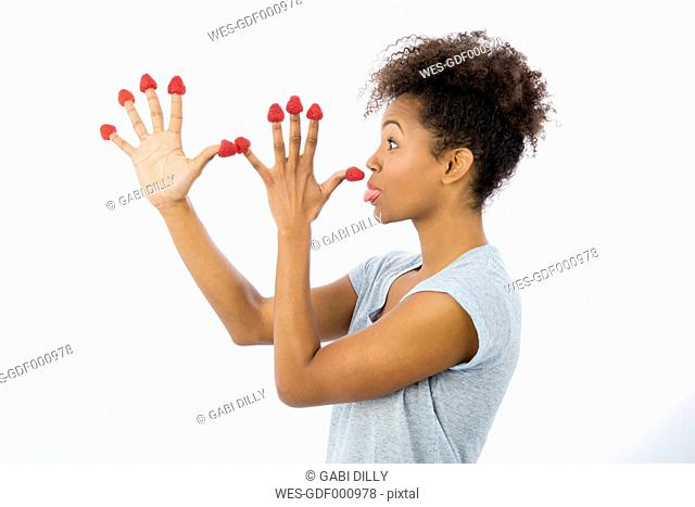 Young woman with raspberries on her fingertips pulling funny faces in front of white background