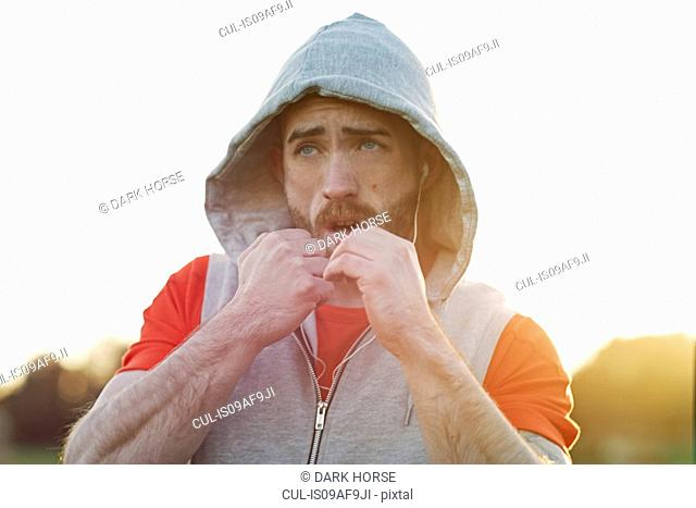 Young man in hooded top boxing training