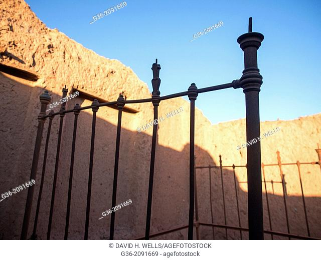 Silhouette of iron bed frame and old wall against blue sky in Agdz, Morocco