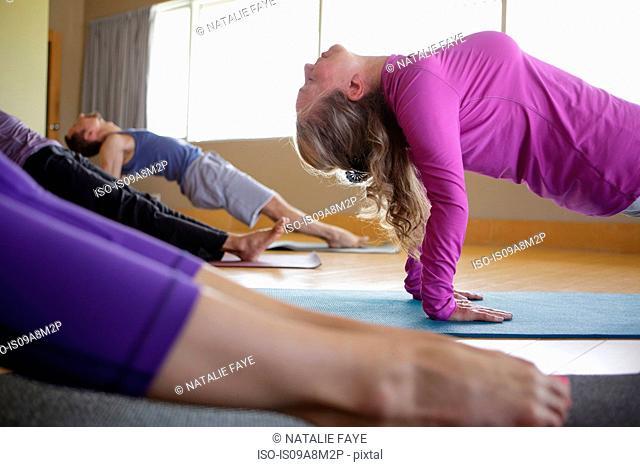 Men and women practicing yoga in studio