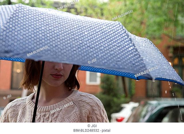 Caucasian woman holding an umbrella in rain