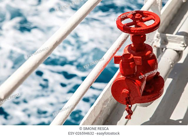 Red fire extinguisher with pipe connector on a boat with waves