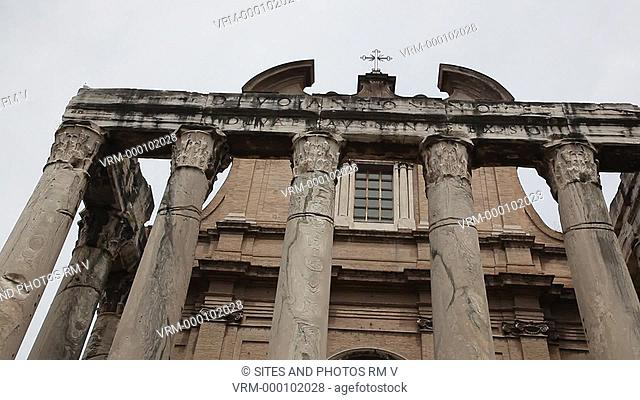 CU, TILT down, Daylight. Exterior, facade. The temple was built by Emperor Antoninus Pius in 141 AD. The facade is preceded by a long stairway with an altar in...