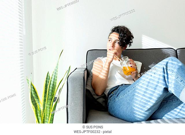 Relaxed young woman sitting on couch with a soft drink