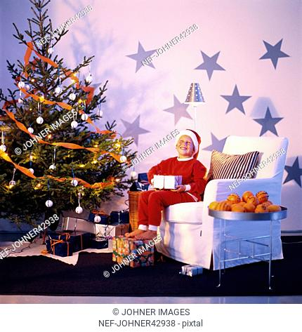 Boy sitting in chair next to the Christmas tree, looks at the presents and smiling