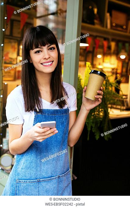 Portrait of smiling woman with cell phone and takeaway coffee in entrance door of a store