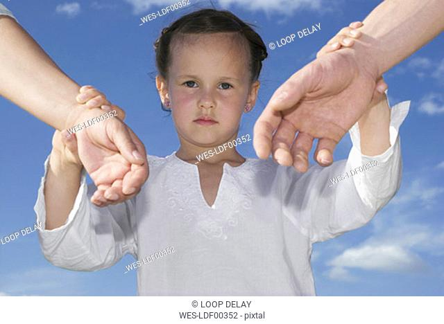 Daughter (7-9) holding hands of parents, close-up
