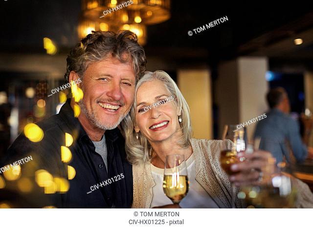 Portrait smiling senior couple toasting white wine glasses in bar