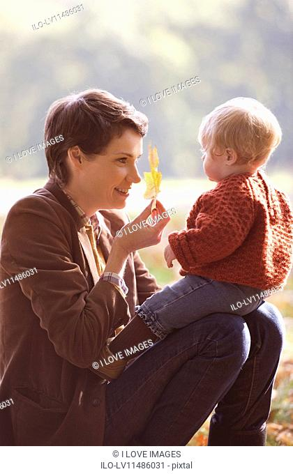 A young mother showing an autumn leaf to her baby