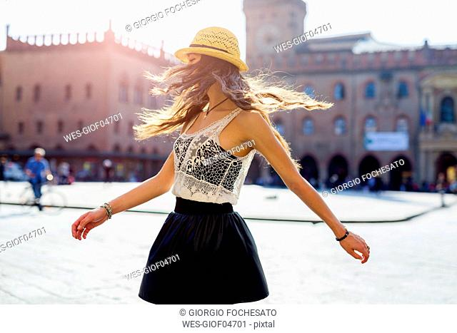 Italy, Bologna, young woman dancing on square
