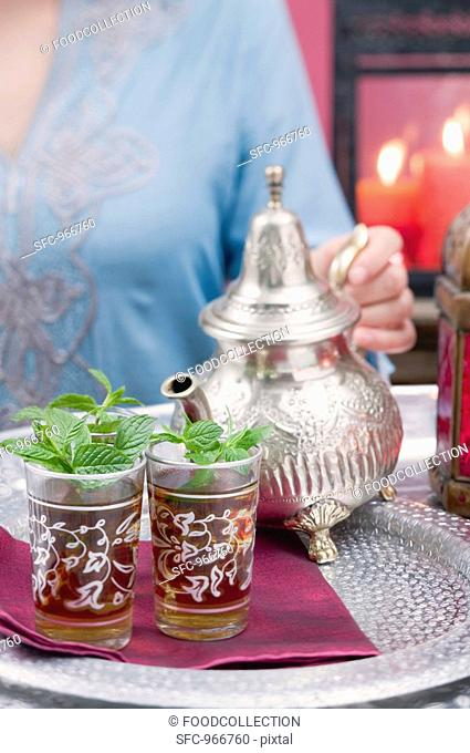 Woman pouring peppermint tea into glasses