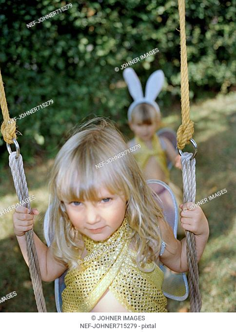 Two dressed up girls by a swing, Sweden