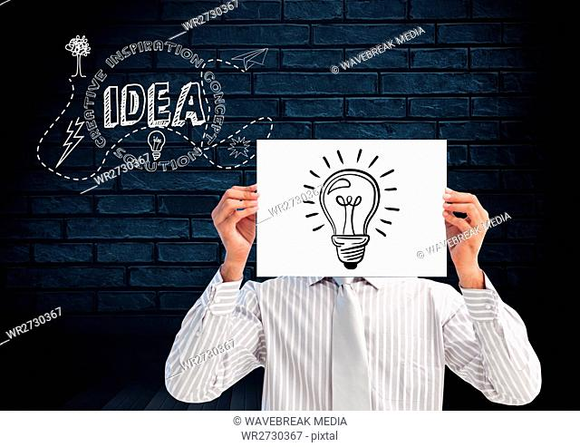 Man holding sheet of paper with drawn light bulb in front of his face and text idea in background