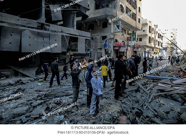 13 November 2018, Palestinian Territories, Gaza: Palestinians inspect the damage of a destroyed residential building after hitting by Israeli air strikes