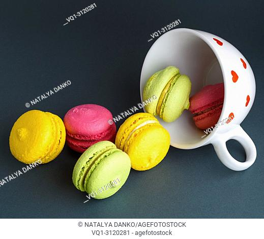 multicolored baked cakes of almond flour macarons in a white ceramic cup on a black background