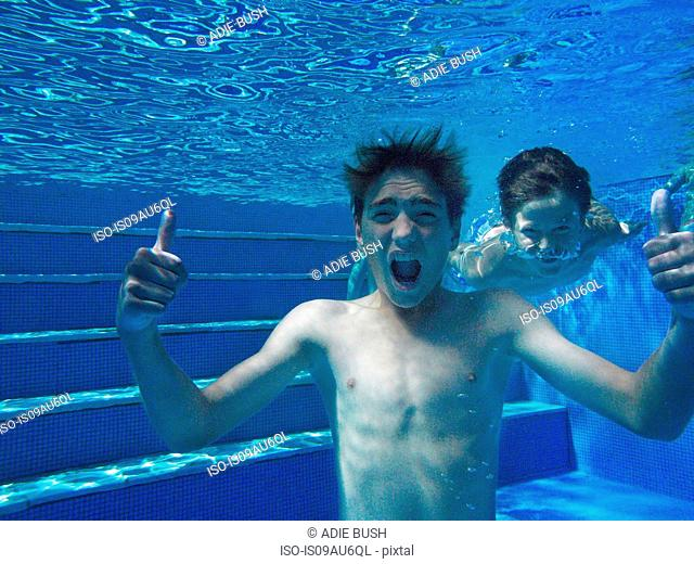 Underwater view of boy giving thumbs up in swimming pool