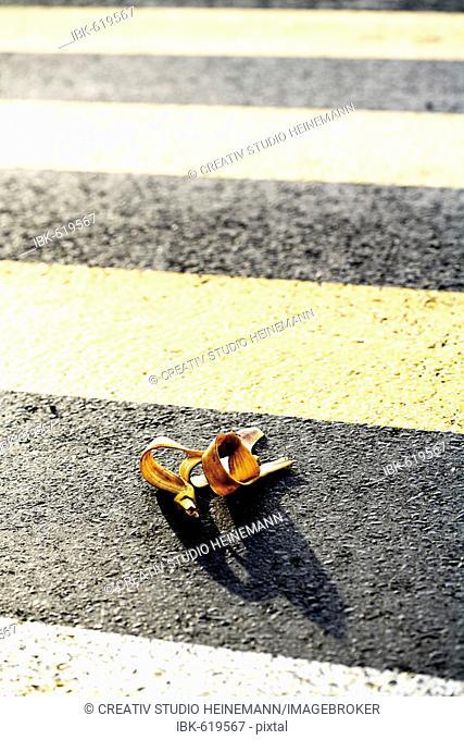 Banana peel on zebra crossing or crosswalk, symbol for accident risk