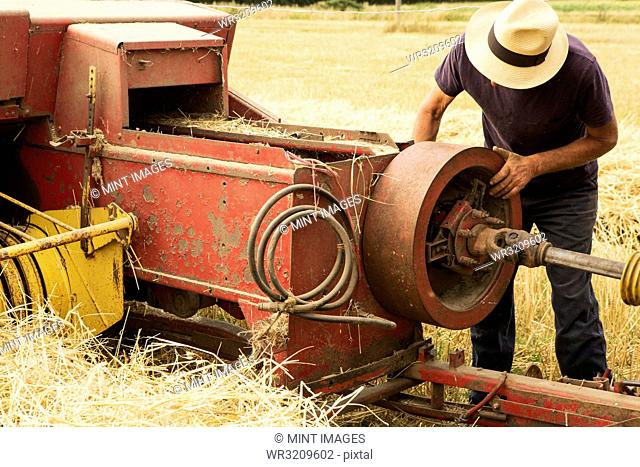 Tractor and straw baler in wheat field, farmer checking equipment