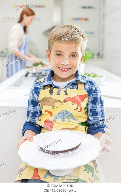 Boy covered in flour holding cake in kitchen