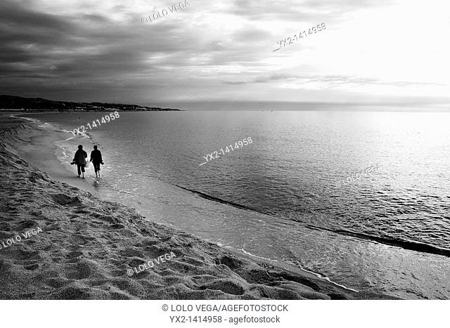 Couple walking on beach, Mataro, Catalonia, Spain