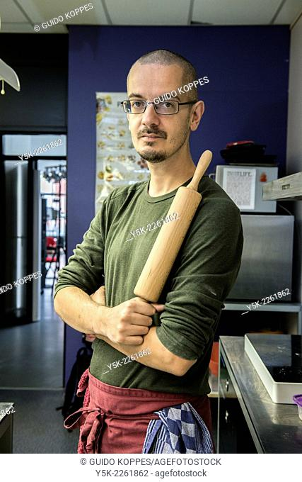 Tilburg, Netherlands. Portrait of an artisan pastry baker with his rolling pin in his kitchen