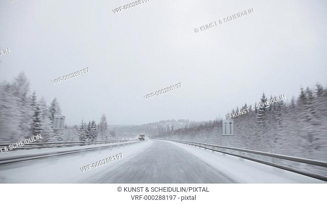 POV-shot of driving in a car on a motorway on a snowy winter day. The car is meeting an oncoming street cleaning vehicle