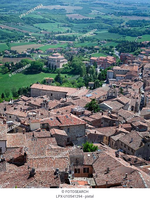 Todi: aerial view of red tiled rooftops, Santa Maria della Consolazione Tempio and Tiber valley beyond, on lovely spring morning, Umbria, Italy