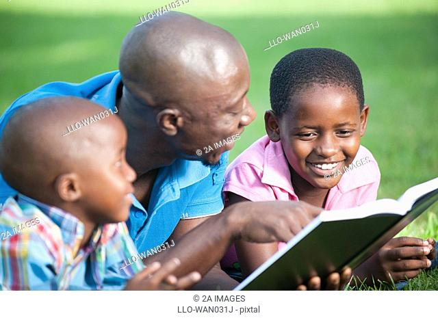 Father reading with children 4-8 on lawn in garden, Johannesburg, Gauteng Province, South Africa
