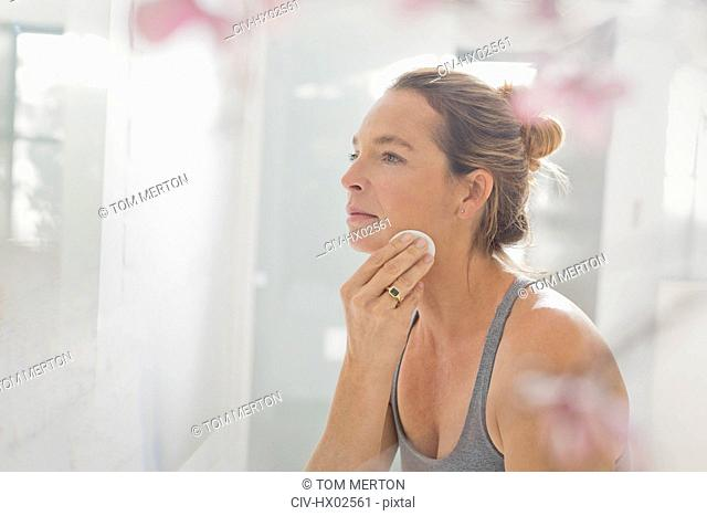 Mature woman applying makeup in bathroom mirror