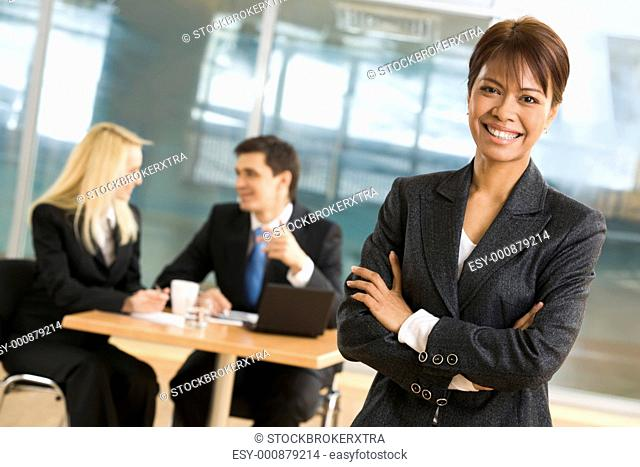 Portrait of beautiful businesswoman standing at foreground of communicating co-workers
