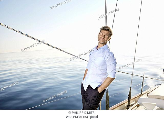 Portrait of smiling mature man standing on his sailing boat