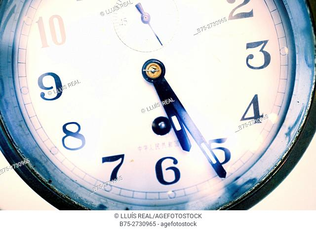 Close up of the face of a clock displaying 5:25