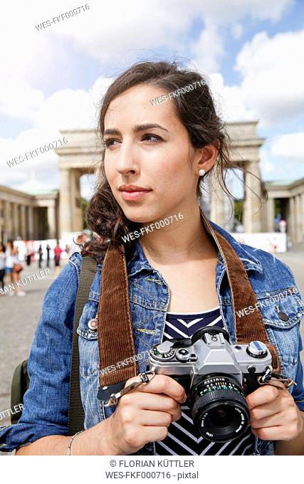 Germany, Berlin, portrait of female tourist with camera