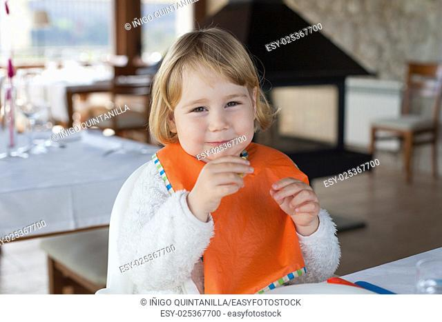 two years old blonde smiling baby with orange bib sitting in table of restaurant looking and eating
