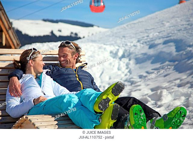 Couple relaxing on wooden chair in ski resort