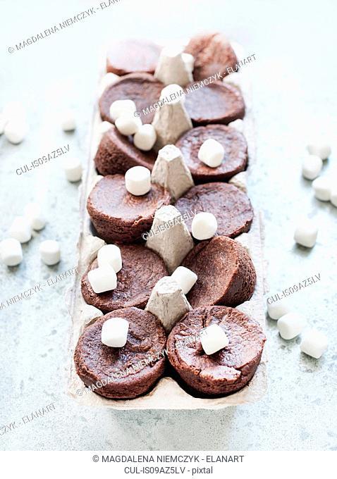 Chocolate brownies and marshmallows in cardboard carton