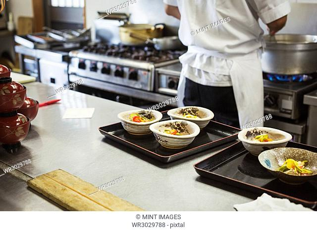 High angle view of trays with bowls of freshly prepared food on the kitchen counter of a Japanese sushi restaurant
