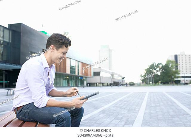 Young male higher education student on bench using touchscreen on digital tablet
