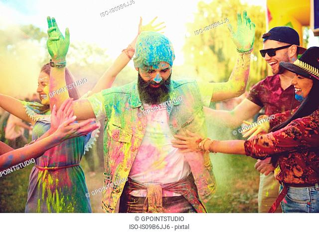 Young adult friends throwing coloured chalk powder and dancing at festival