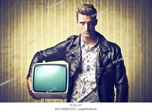 Young man holding old TV