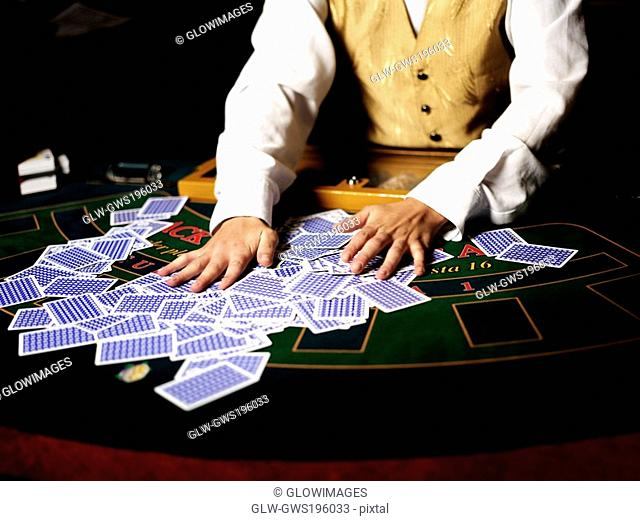 Mid section view of a casino worker shuffling playing cards on a gambling table